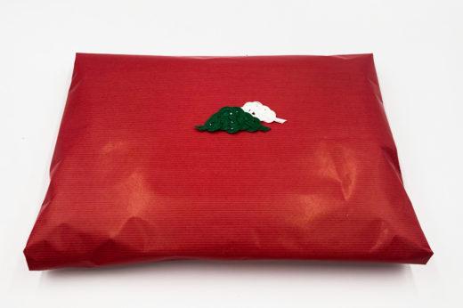 真っ赤な包装紙に白と緑の若松を結んだ水引をポチッと。