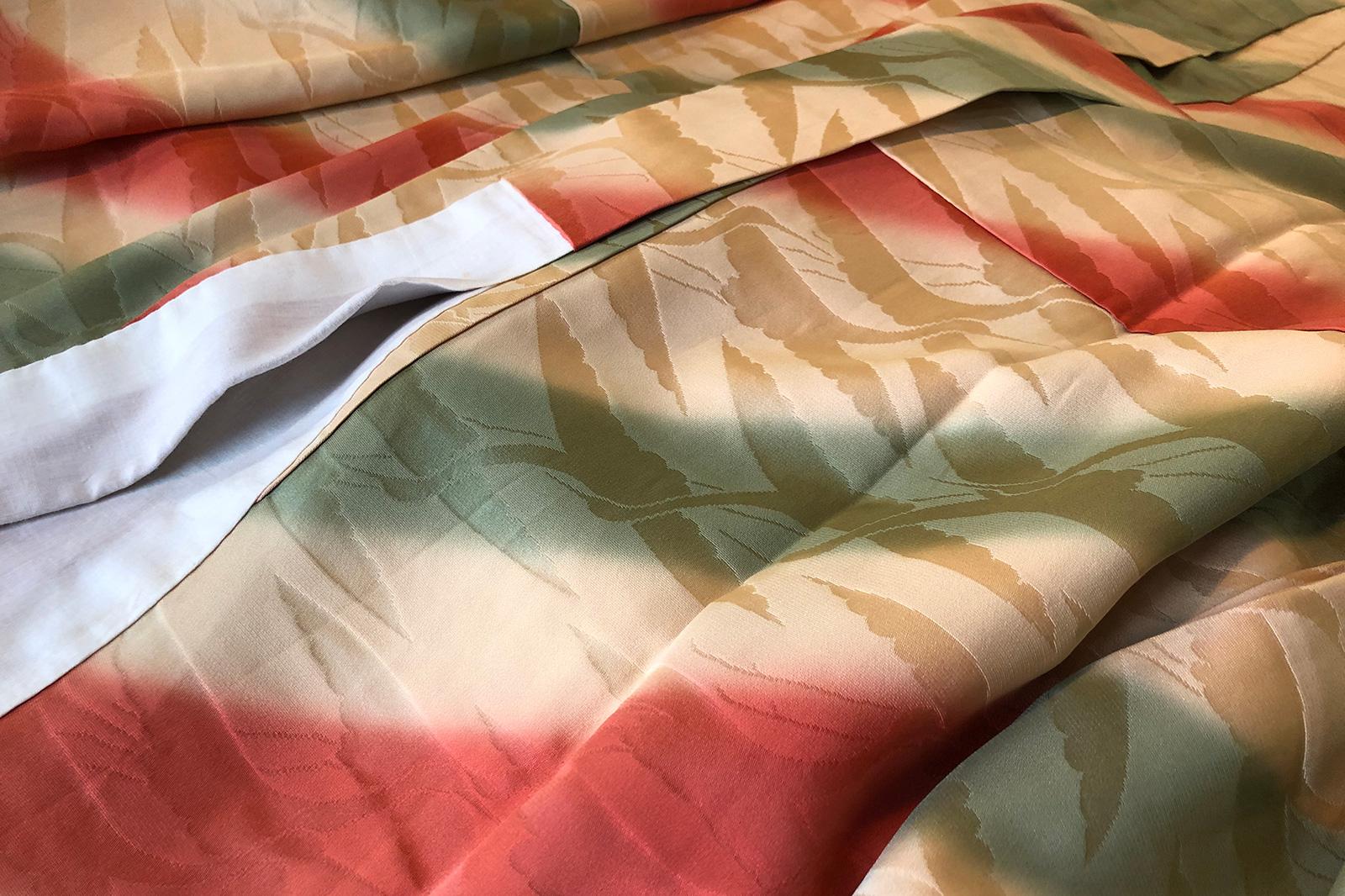 鶴の羽ばたく字模様に赤と緑で手綱取り。